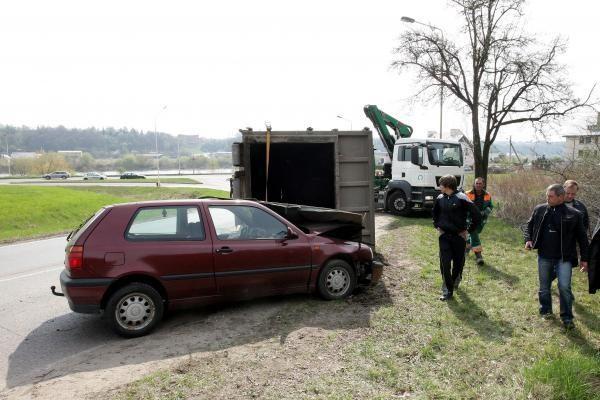 Konteineris užvirto ant pravažiuojančio automobilio